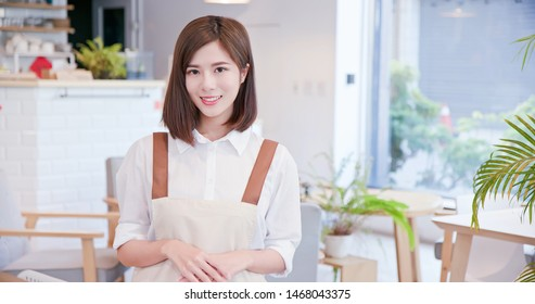 young asian shopkeeper smile to you in her restaurant