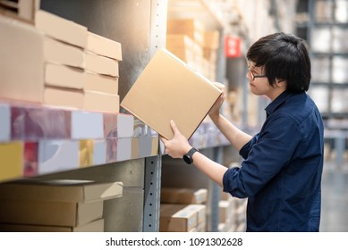 Young Asian shopper man picking cardboard box package from product shelf in warehouse. Male customer shopping lifestyle in department store. Buying or purchasing factory goods. Shopaholic concepts