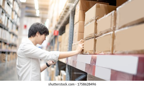 Young Asian shopper man picking cardboard box package from product shelf in warehouse. Male customer shopping lifestyle in department store. Buying or purchasing factory goods. Inventory stock concept