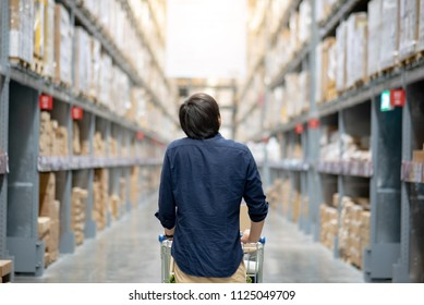 Young Asian shopper man walking with shopping cart (trolley) through aisle in warehouse choosing what to buy. Shopping lifestyle in department store. Buying or purchasing factory goods.