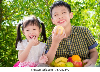 Young asian siblings eating fruits together in park