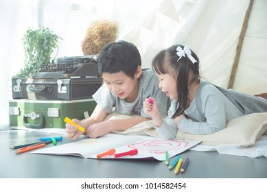 Young asian siblings lying on the floor and drawing picture by crayon at home