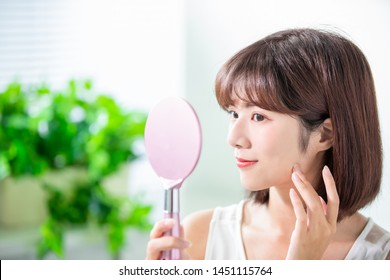 Young asian skin care woman smile and look mirror