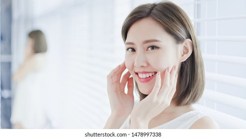 Young asian skin care woman happily touch her face and enjoy herself