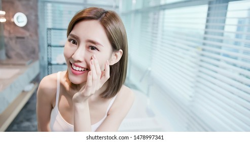 Young asian skin care woman happily touch her health eye