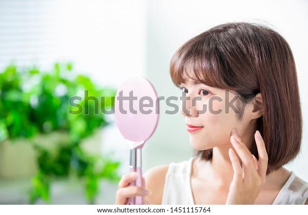 若いアジアのスキンケア女性の笑顔とルックミラー