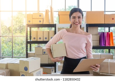 Young Asian small business owner at home office, online marketing packaging and delivery scene, startup SME entrepreneur or freelance woman working at home concept , Home online business , Delivery