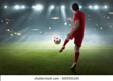 Young asian soccer player shooting the ball on the match