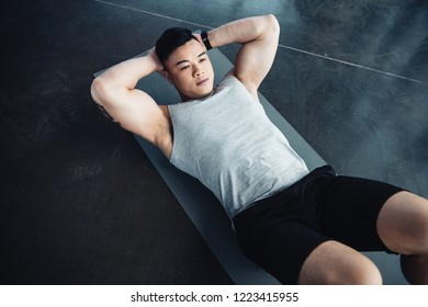 young asian sportsman doing abs exercise on fitness mat at gym