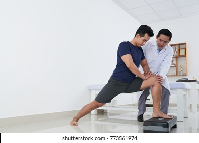 Young Asian sportsman doing exercise under control of physiotherapist