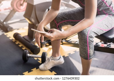Young asian sportswoman sitting and using smartphone in gym