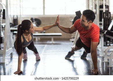 Young Asian sporty couple sit up exercise together at gym, Fitness man and woman giving each other a high five during the training session in gym. Sport and healthy lifestyle.