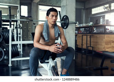 Young asian sporty man tired sitting with towel after gym workout in fitness.