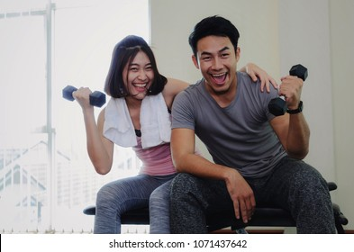 young asian sporty man and woman love couple doing exercises with dumbbell, cheer up and smiling after good workout in fitness gym, slim bodybuilder, healthy lifestyle and sport training concept