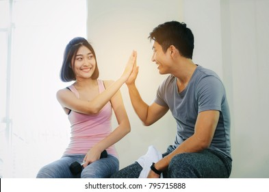 young asian sporty man and woman love couple cheering, smiling and giving high five together after good workout in fitness gym, slim bodybuilder, healthy lifestyle, exercise and sport training concept