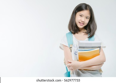 Young Asian student girl holding books on isolated background