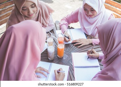 young asian student with head scarf studying together in a cafe