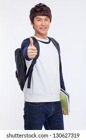 Young Asian student showing thumb isolated on white background.