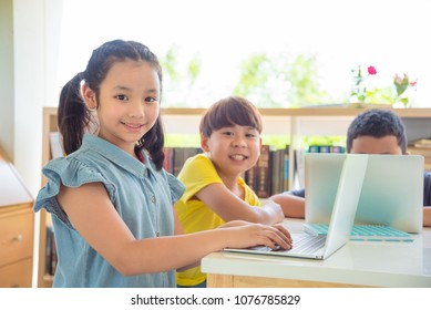 Young asian student using laptop computer in school library