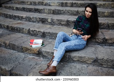 Young asian student using mobile phone during her class break at university school sitting on the steps, student girl browsing the internet with her cell phone, technology and communication concept
