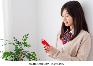 young asian student using smart phone in the white room
