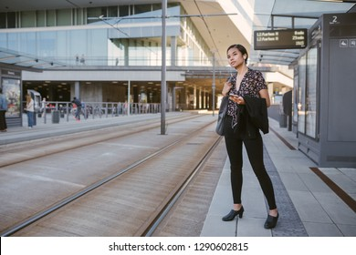 Young Asian student waiting at a tram stop in the city listening to music on earphones during her morning commute