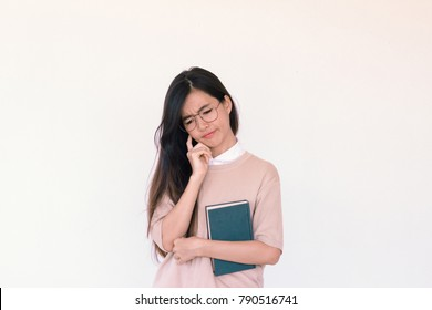 Young asian Student woman holding book and question marks doodles at the back ground with copy space