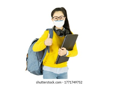 Young asian student woman in yellow shirt and glasses wearing medical face mask,carrying a bag and laptop to go to school Under the outbreak of the virus isolated on white background