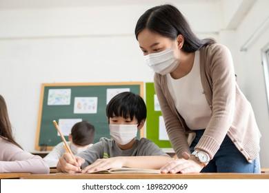 Der junge Asienlehrer mit einem kleinen Jungen, der Schutzmasken trägt und während der COVID-19-Pandemie im Klassenzimmer studiert. Studentenschülerinnen in der internationalen Schule