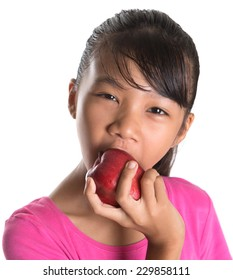 Young Asian teen eating a red apple over white background