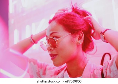 Young asian teen girl in street fashion style with sunglasses, neon light pink background, night life and fashion lifestyle