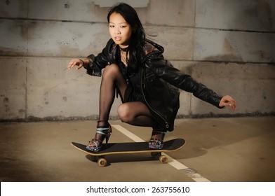 Young asian teen riding a skateboard