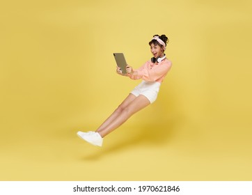 Young asian teenage girl hand holding computer laptop floating in mid-air isolated on yellow background. Fast internet concept.