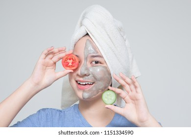 young Asian teenage girl hold tomato and cucumber, smile happy face masking cream on face and towel on head. woman beauty shot with idea of skin care nutrition. suitable for skin care cosmetic product