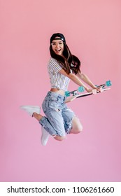 Young asian teenage girl on pink background. Stylish young woman with skateboard isolated.