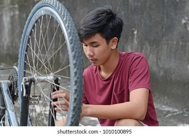 Young asian teenager checking an old bicycle.