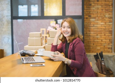 Young asian teenager owner business woman work at home  for online shopping reading and writing the order with digital tablet, preparing package the product, entrepreneur alpha generation life style