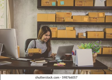 Young asian teenager owner business woman work at home for online shopping, checking order and prepaing package the product with office equipment, entrepreneur and alpha generation life style concept