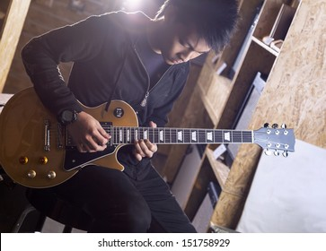 A young asian teenager playing electric guitar with a spotlight shining from the back.