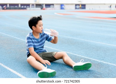 Young Asian Thai boy drinking water from bottle during resting on the blue track after running