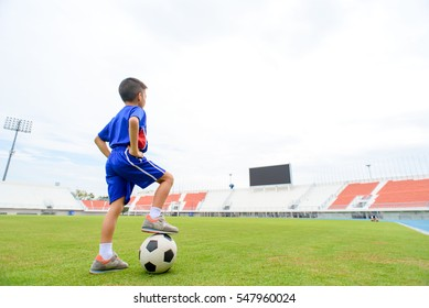 Young Asian Thai boy play on the grass football field in the stadium during summer