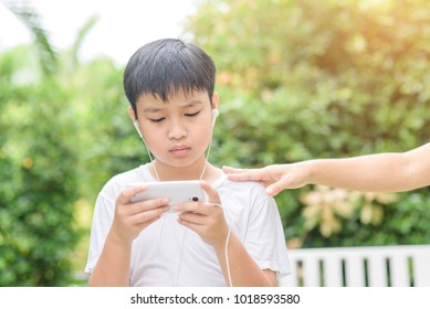 Young Asian Thai boy using a smartphone to play game and listen to music without care the surrounding.