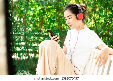 Young Asian Thai woman listen to music from headphone and relax at home.