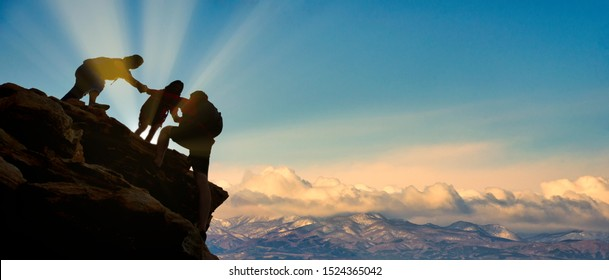Young asian three hikers climbing up on the peak of mountain near  himalaya mountains. People helping each other hike up a mountain at sunrise. Giving a helping hand. Helps and team work concept