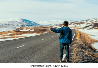 Young asian tourist in blue jacket hitchhiking on the road during vacation trip in iceland.