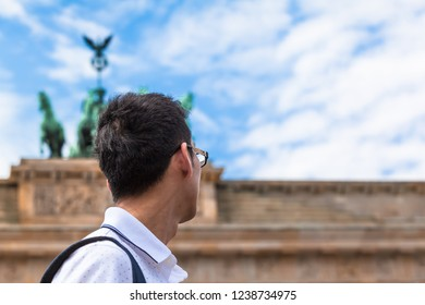 Young asian tourist or business man in Berlin (Germany) looking up to statue of Brandenburg Gate (copy space)