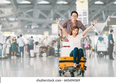 Young Asian tourist couple happy and excited together for the trip, girlfriend sitting and cheering on baggage trolley or luggage cart. Holiday vacation traveling abroad concept, with copy space