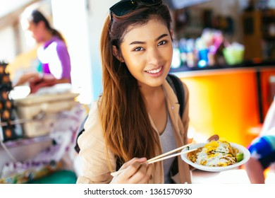 Young Asian tourist woman eating pad thai noodle, traditional street food in Thailand and looking at camera