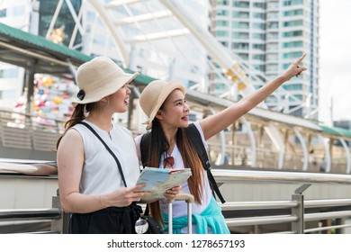 Young Asian tourist woman pointing at the building while her friend looking and holding a map