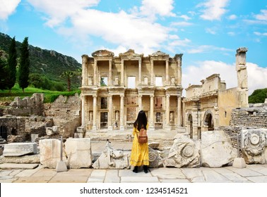 A young Asian tourist woman wearing yellow dress enjoying the view at Library of Celsus at Ephesus which is an ancient Roman building in Ephesus, Anatolia and now part of Selçuk, Turkey.